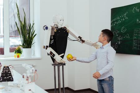 Weź to. Szczęśliwy ładny chłopiec trzyma jabłko, jednocześnie dając go robotowi
