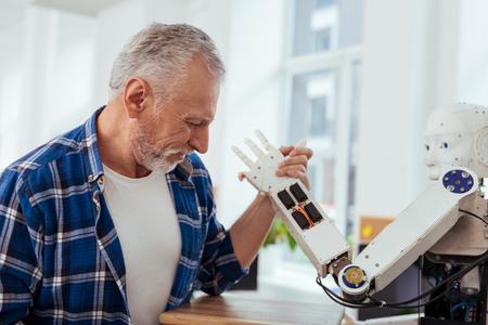 Humor positivo. Hombre positivo feliz sonriendo mientras hace armrestling con un robot