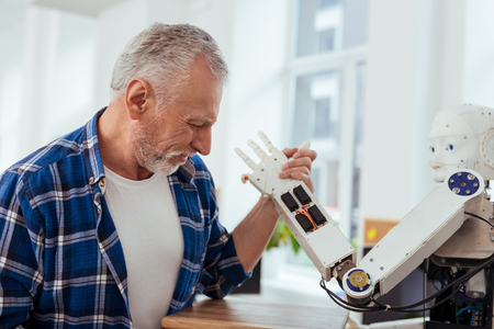 Positive mood. Happy positive man smiling while doing armwrestling with a robot