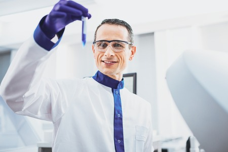 Work with pleasure. Cheerful practitioner raising his arm while looking at test tube