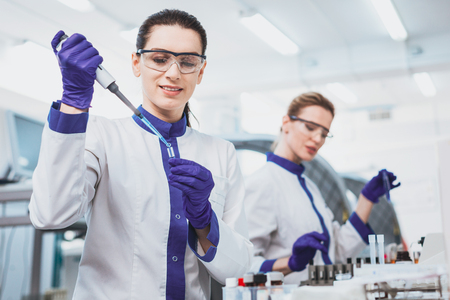 Protective glasses. Silhouette of attentive researcher that taking test tube while doing chemical analysis Stock Photo