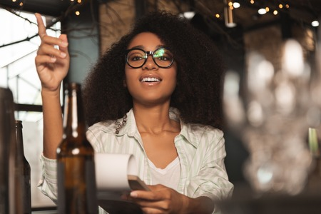 Best service. Pleasant curly woman holding a menu and placing an order at the bar while talking to the barman Stock Photo