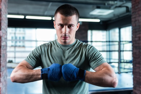 Young athlete. Dark-eyed young athlete wearing blue wrist wraps before boxing and training in gym