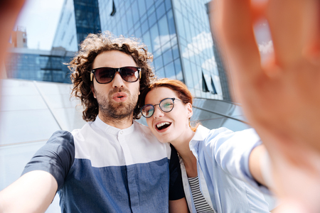 Laughing couple. Young stylish modern couple wearing glasses laughing while making selfie for beautiful memories