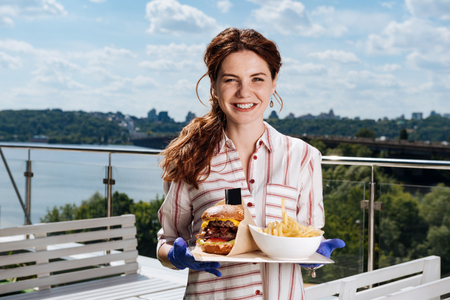 Woman with ponytail. Smiling woman with ponytail feeling rested while eating potatoes and meat burger Stock Photo - 104841307