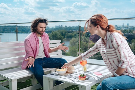 Fries of man. Red-haired woman eating fries of her man during dinner while having not very good manners Stock Photo