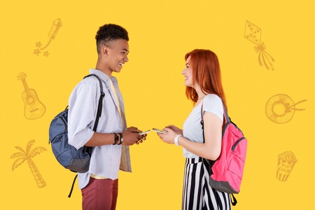 Finding common ground. Cheerful easy going students standing opposite each other with smartphones in their hands and smiling while getting acquainted
