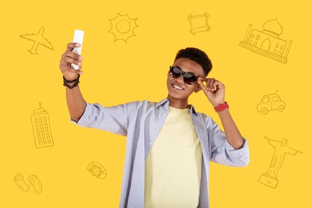 Feeling good. Positive relaxed student feeling good at the seaside and touching his sunglasses while taking a selfie