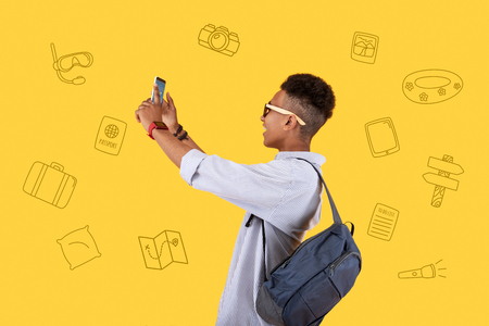 Going sightseeing. Cheerful happy teenager holding a modern smartphone and standing with a backpack on his shoulder while taking photos during his amazing journey Standard-Bild - 104867483