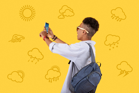 Sunny day. Emotional teenager standing with a modern smartphone in his hands and smiling while enjoying sunny weather and taking photos of the sky Standard-Bild - 104867484
