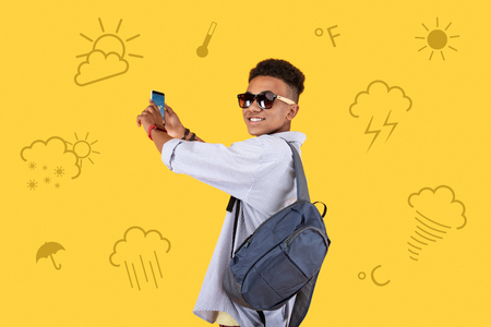 Good weather. Attentive positive teenager wearing sunglasses and standing with a modern gadget in his hands while enjoying sunny weather and taking photos Standard-Bild - 104867485