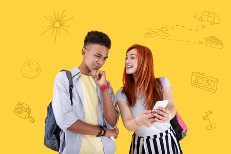 Please look. Calm student touching his chin and his girlfriend feeling excited while showing him her photos from the journey
