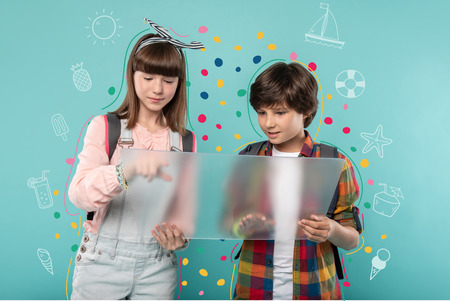 Transparent device. Positive friendly teenagers standing close to each other and thoughtfully looking at the transparent gadget