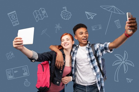 Say cheese. Cheerful young friends holding two modern gadgets and smiling while taking selfies Stock Photo