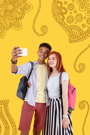 Say cheese. Cute young couple of teenagers hugging and kindly smiling while taking selfies with a help of a modern smartphone Stock Photo