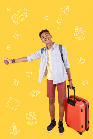 Happy hitchhiker. Positive experienced hitchhiker holding a big suitcase and feeling confident while putting his thumb up and trying to catch a car on the road Imagens