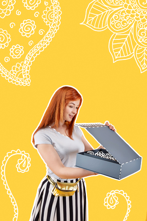 Unusual present. Calm young girl feeling pleased while opening a big box and looking at the beautiful present Stock Photo