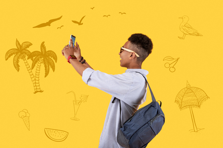 Holidays photos. Positive active tourist traveling in exotic places and feeling glad while taking photos with a help of his modern smartphone Standard-Bild - 104902060