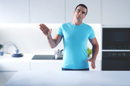 Switched off humanoid. Futuristic useful home humanoid standing in the laconic kitchen with his hands up while being switched off Banco de Imagens