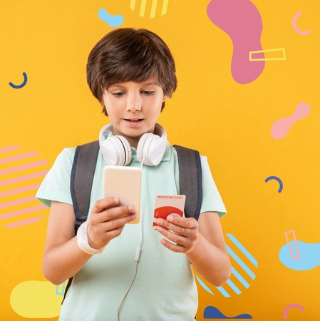 Discount card. Calm attentive boy standing with a modern gadget and looking at the screen of it while using a new discount card Stock Photo