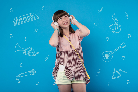 Peaceful sounds. Relaxed young girl smiling and looking into the distance while standing with big headphones and listening to music Stock Photo