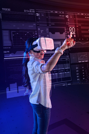 Impressed girl. Clever progressive kid standing in front of a transparent screen and opening her mouth while feeling impressed by the opportunities of a virtual reality device Stock Photo