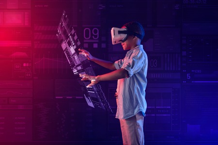 Illuminated projection. Calm clever progressive boy wearing virtual reality glasses and feeling interested while creating a detailed hologram