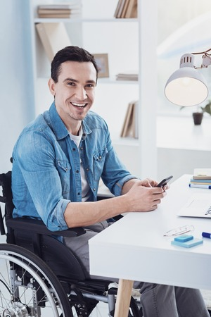 Look at me. Joyful disabled man expressing positivity while sitting on his wheelchair