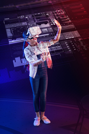 Detailed projection. Smart progressive girl wearing virtual reality device and feeling interested while wearing modern virtual reality glasses
