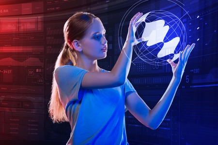Realistic projection. Clever progressive schoolgirl carefully holding a transparent projection of the Earth and looking at it Stock Photo