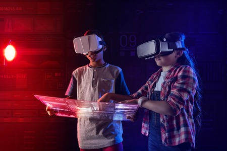 Careful kids. Calm friendly kids standing with a transparent tablet in their hands and touching the screen of it while wearing virtual reality glasses Stockfoto