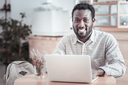 Young freelancer. Happy positive bearded man sitting at the table and smiling while working on a netbook