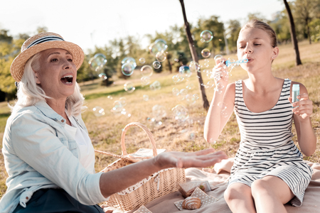 Lets play. Surprised mature woman opening her mouth while playing with her granddaughter and being together in the park Stock Photo