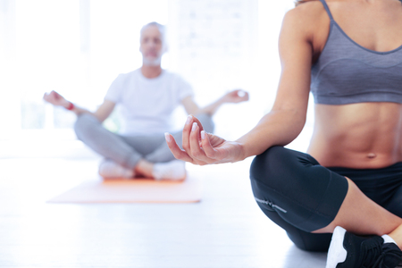 Keep your balance. Relaxed male person putting elbows on knees and crossing legs while meditating