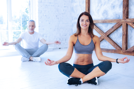 Good mood. Cheerful female person expressing positivity and crossing legs while sitting in yoga pose