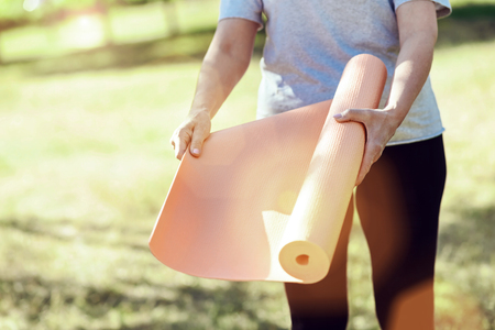 Yoga mat. Beautiful convenient yoga mat being in the hands of an active energetic woman