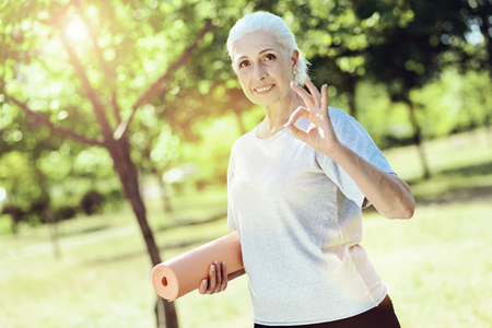 All right. Pretty positive senior woman expressing her cheerful mood while being in a beautiful green park Banco de Imagens