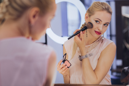 Exciting date. Gorgeous prosperous businesswoman getting ready for exciting date while making up