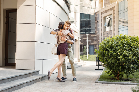 My dear. Nice delighted man hugging her girlfriend while being happy to see her