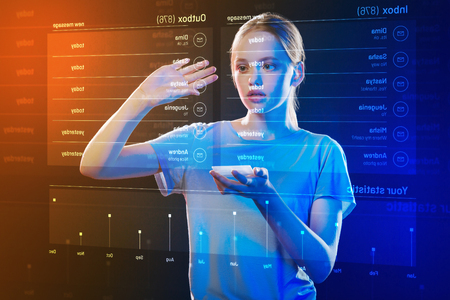Careful girl. Calm clever progressive girl standing with a modern device in her hand and carefully touching the icon on a holographic projection Stock Photo