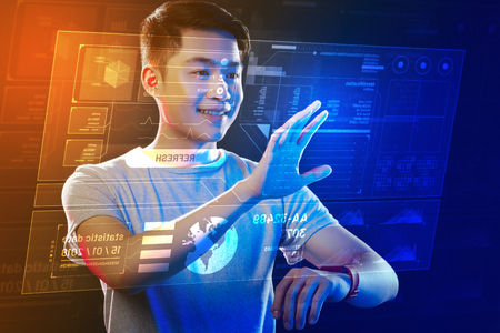 Holographic screen. Positive confident software developer smiling and touching the projection while creating it with a help of a smart watch Foto de archivo