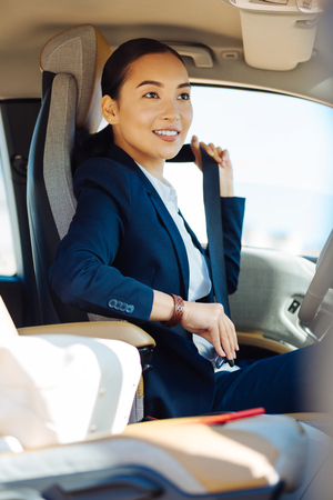 Joyful mood. Joyful happy woman smiling while fastening her seatbelt Banco de Imagens