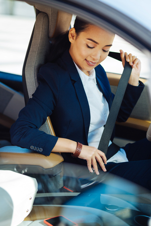 Safety rules. Positive young woman wearing a seatbelt while driving safe