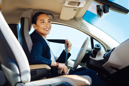 Happy positive woman smiling while fastening the seatbelt