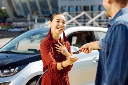 Positive young woman looking at her boyfriend while taking the key from the car