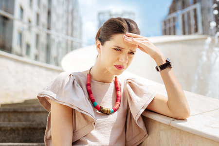 Difficult time. Depressed unhappy woman touching her forehead while thinking about her problems