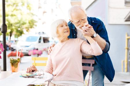 So romantic. Galant senior man meeting his wife who sitting Imagens