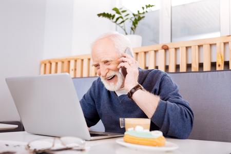 Fruitful cooperation. Joyful senior freelancer using laptop and communicating on phone
