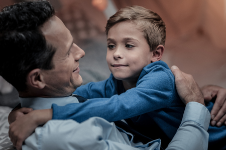 Cheerful schoolboy expressing positivity while embracing his father Stock Photo