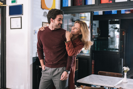 Surprise darling. Jolly optimistic woman touching man and grinning